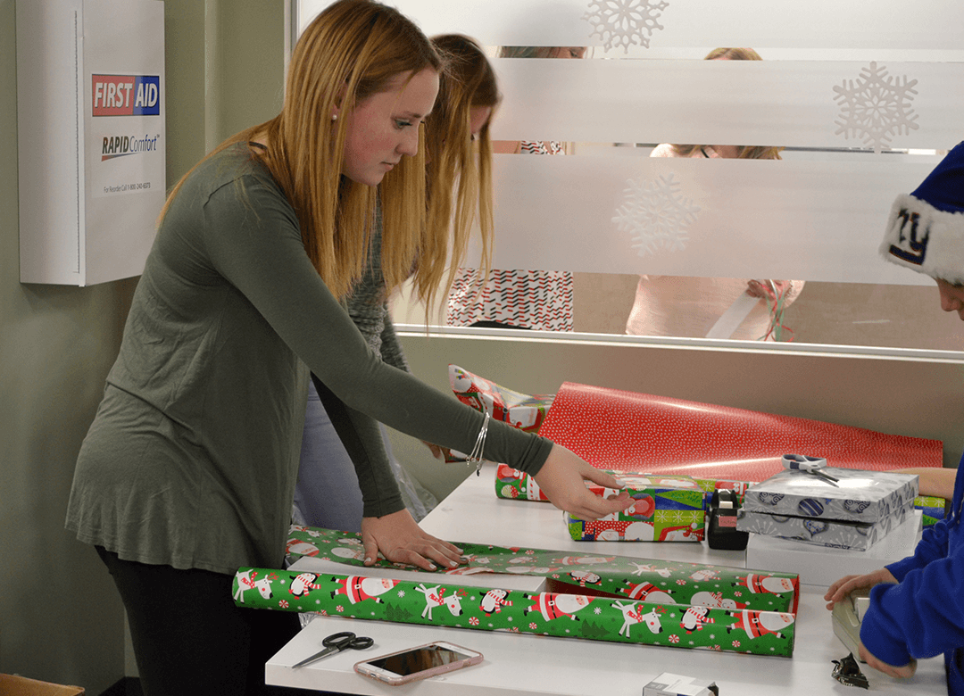 workers wrapping gifts during rose's care and share event